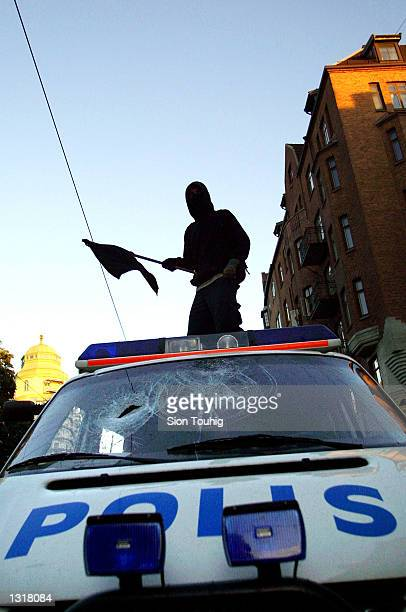 An anarchist demonstrator climbs on a damaged police van June 15 2001 in Gothenberg Sweden as fighting breaks out at a demonstration against the EU...
