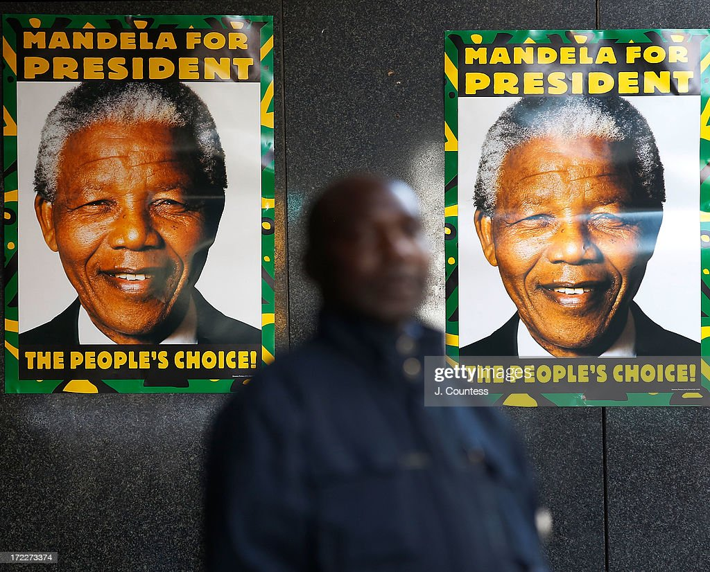 An ANC worker stands between classic 'Mandela for President' posters hung outside ANC headquarters prior to an African National Congress-sponsored prayer rally outside ANC headquarters on July 2, 2013 in Johannesburg, South Africa. The anti-apartheid icon and Nobel Peace Prize Laureate has been in the hospital for more than three weeks being treated for a recurring lung infection.