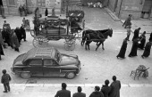 An ancient horsedrawn hearst and a car leading the funeral procession Sicily March 1958