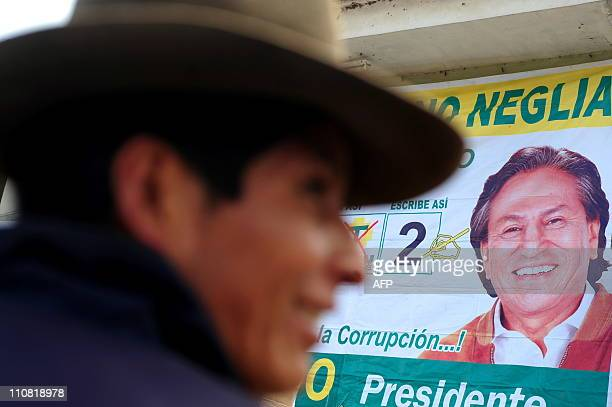 An Andean man passes by a propaganda placard of the presidential candidate for the 'Peru Posible' party former Peruvian president Alejandro Toledo...