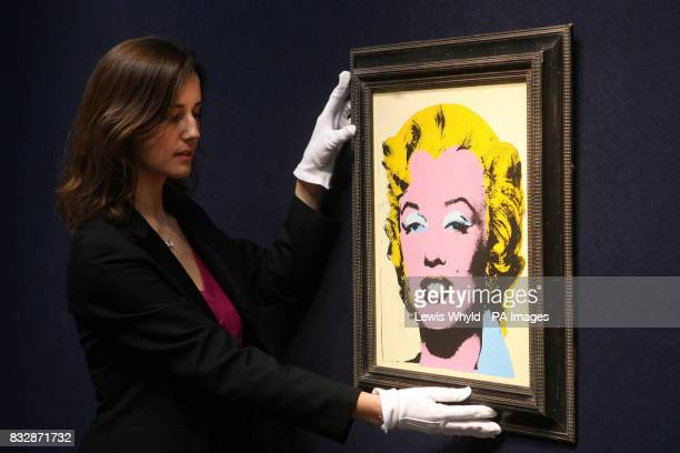 An Andy Warhol portrait of Marilyn Monroe titled Lemon Marilyn is adjusted at Christie's in London before the Christie's PostWar and Contemporary Art...