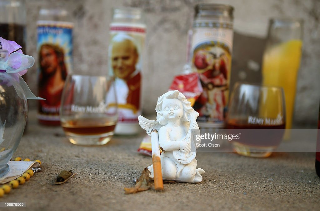 An angel, a cigarette, liquor and religious candles help to form a memorial created in an alley near the spot where 20-year-old Octavius Dontrell Lamb was shot yesterday and killed, on January 2, 2013 in Chicago, Illinois. At 3:45 a.m., less than four hours into the new year, Lamb became the first murder victim of 2013 in Chicago, a city which saw more that 500 murders in 2012. Fifteen people were shot in Chicago on the first day of the year, three fatally. Aurora, Illinois' second largest city, had no murders in 2012.