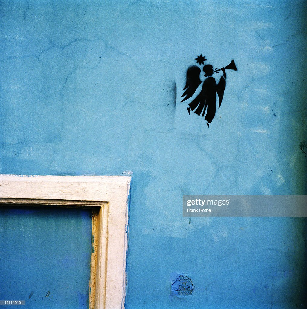 an angel painted on a blue wall : Stock Photo