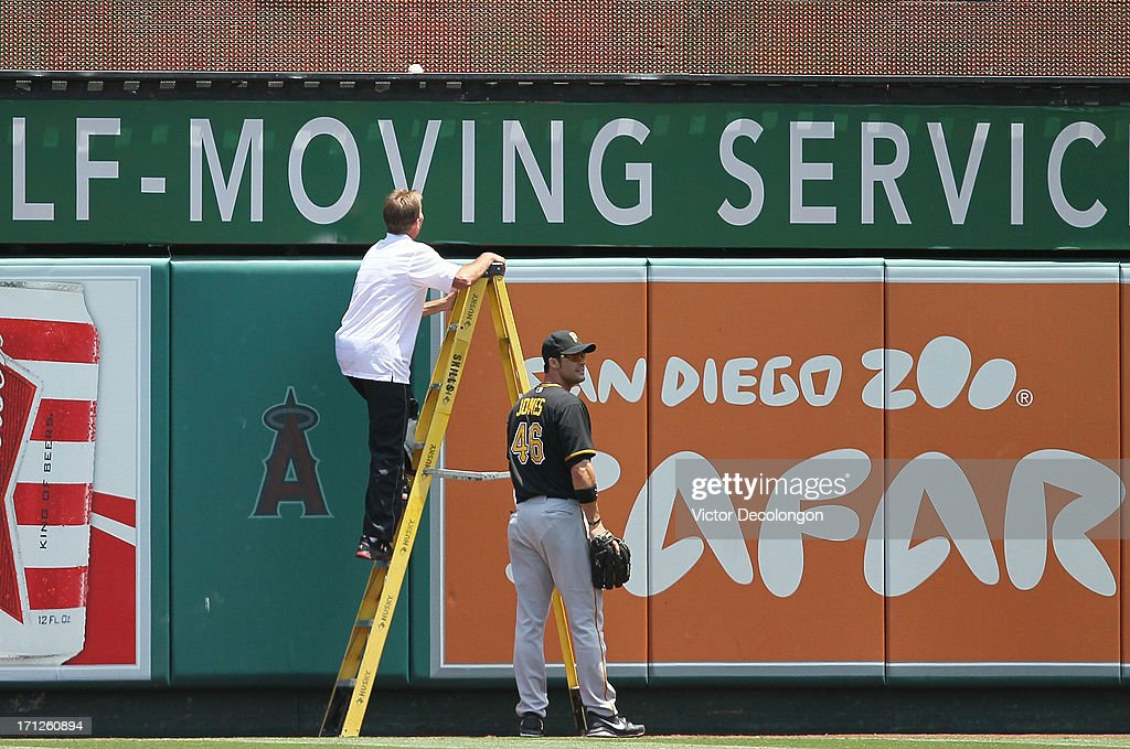 An Angel Stadium of Anaheim grounds crewman walks up a ladder to retrieve the game ball after it became lodged at the bottom of the right field scoreboard as outfielder Garrett Jones #46 of the Pittsburgh Pirates looks on in the middle of the second inning during the MLB game at Angel Stadium of Anaheim on June 23, 2013 in Anaheim, California. The ball was hit by Tony Sanchez #59 of the Pittsburgh Pirates and was ruled a ground rule double. The Pirates defeated the Angels 10-9 in ten innings.