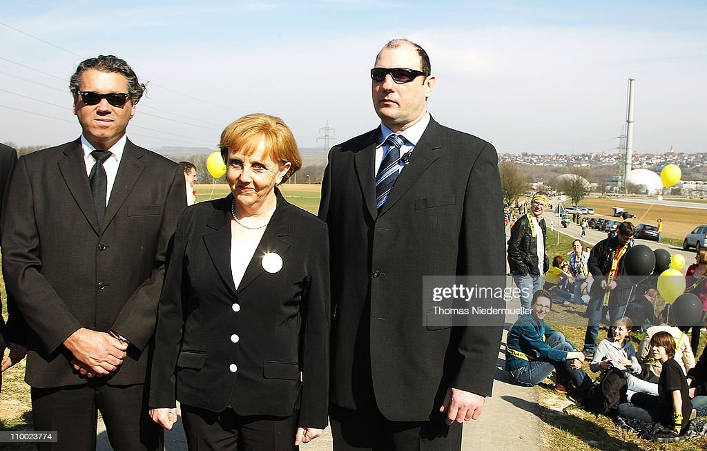 An Angela Merkel double poses with bodyguards in front of the Neckarwestheim nuclear power plant on March 12, 2011 near Neckarwestheim, Germany. Activists were protesting against the government-granted extension of the operational timespan of several of Germany's older nuclear power plants, which Chancellor Merkel's government claims is necessary to bridge demand before planned renewable energy projects begin operation. The activists claim their call for an end to nuclear power is all the more vital given the current, potential catastrophe brewing at at least one reactor at the tsunami-damaged Fukushima facility in Japan.