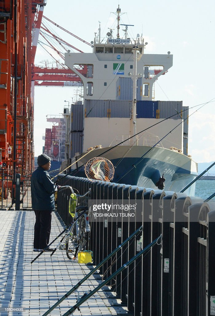 An angler fishes before an international freighter at a container terminal at the Tokyo port on December 10, 2012. Japan confirmed that the world's third-largest economy shrank in the three months to September, stoking fears the country is slipping into a recession. Financial turmoil in Europe, a strong yen that has dented exports and a painful diplomatic row with major trade partner China have dented Japan's economy. AFP PHOTO / Yoshikazu TSUNO
