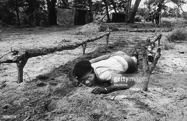 An Angolan soldier crawls beneath barbed wire trenches during training Dr Jonas Savimbi and his UNITA movement is doing well in its fight against the...