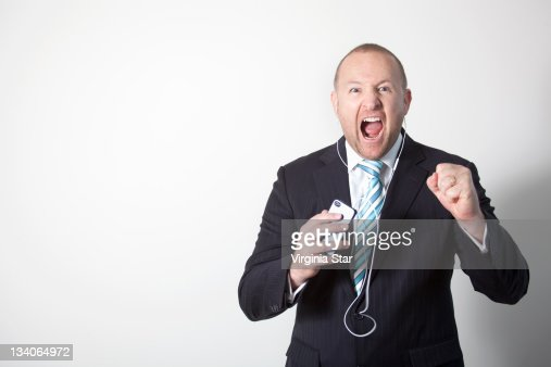 An angry businessman yelling on a smart phone : Stock Photo