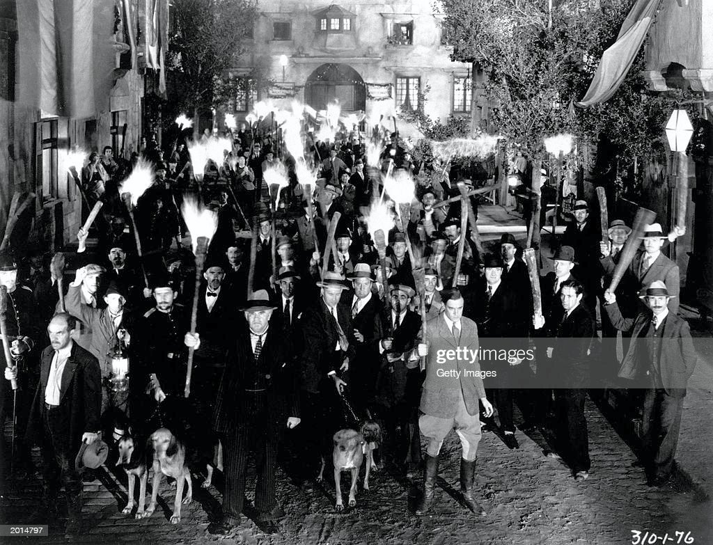 An angry mob holding torches in a still from the film 'Frankenstein' directed by James Whale 1931