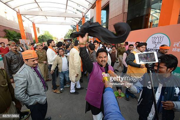 An angry over ticket distribution a BJP supporter shows a black flag to the party's National President Amit Shah after releasing the party's...