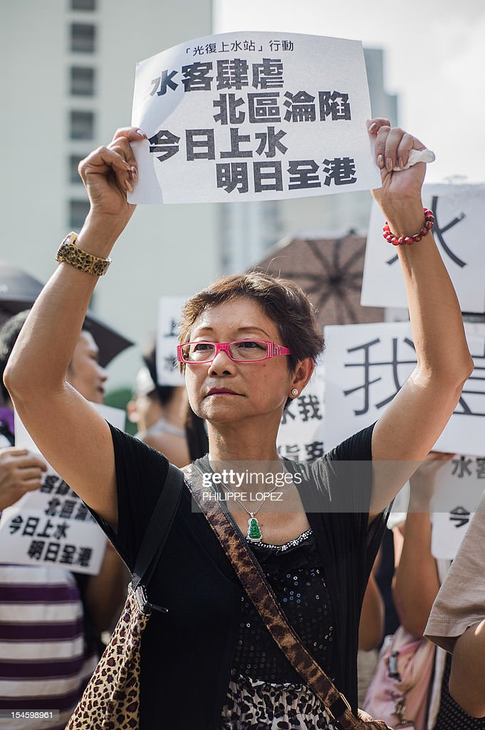 An angry resident of the border town of Sheung Shui holds a printed slogan during a protest in Hong Kong on October 23, 2012 against the thousands of mainland Chinese who travel across the border every day to buy products to resell at a profit in China. The so-called parallel traders typically travel to Hong Kong by train and stock up on everything from iPads to milk powder, taking advantage of lower prices and wider choice in the city and dodging hefty tariffs on their return. AFP PHOTO / Philippe Lopez