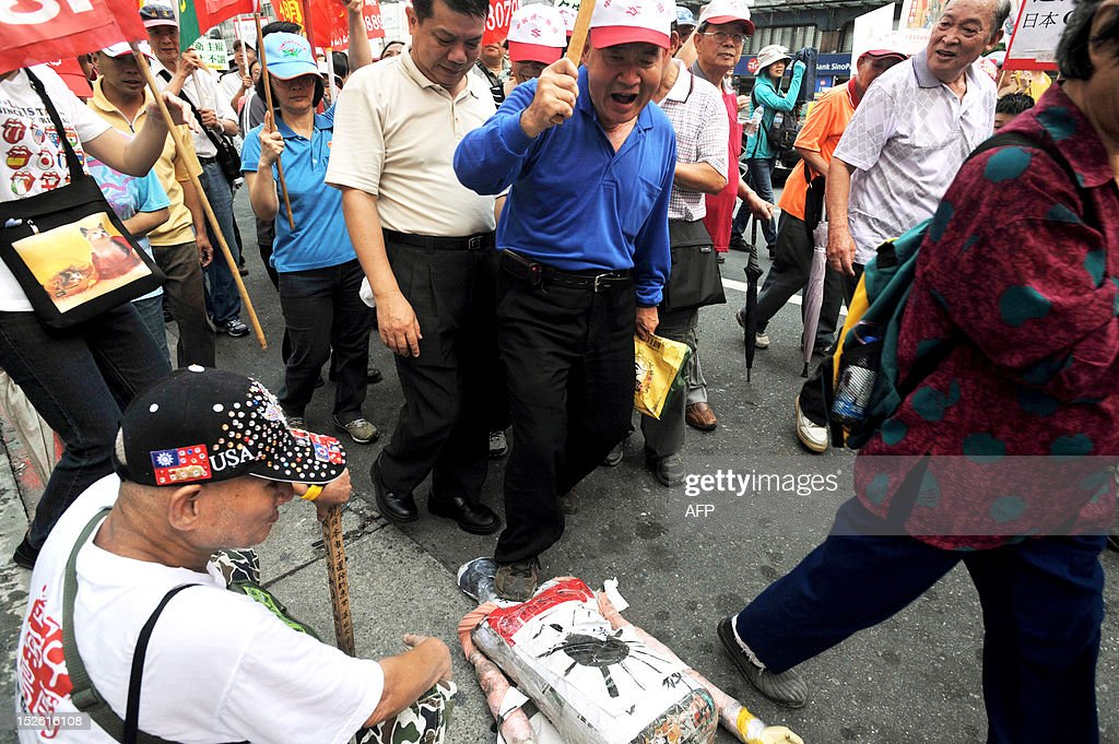 An angry Taiwanese demonstrator tramples on a paper-made doll of Lee Teng-hui, former Taiwan president known for his pro-Japanese political stance, during a demonstration in Taipei on September 23, 2012, over a territorial dispute on the island group in the East China Sea. Lee drew fire after telling a Japanese magazine in September that the disputed archipelago belongs to Japan. Hundreds of slogan-chanting Taiwanese activists and their supporters rallied against Japan amid the territorial dispute over the Senkaku island group controlled by Japan, which is also claimed by China and Taiwan under the name Diaoyu. AFP PHOTO / Mandy CHENG