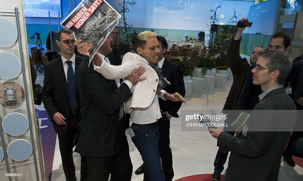An animal rights activist displaying a placard reading: 'we are sick of (German Agriculture Minister Ilse) Aigner' is dragged away by security after he barged in on Aigner as she toured the German agriculture ministry's hall at the Gruene Woche (Green Week) Agricultural Fair in Berlin on January 17, 2013.