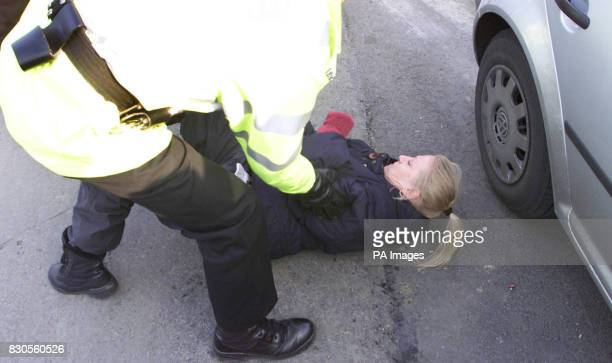 An animal rights activist is stopped by a policeman outside the pharmaceutical firm Huntingdon Life Sciences headquarters in Huntingdon...