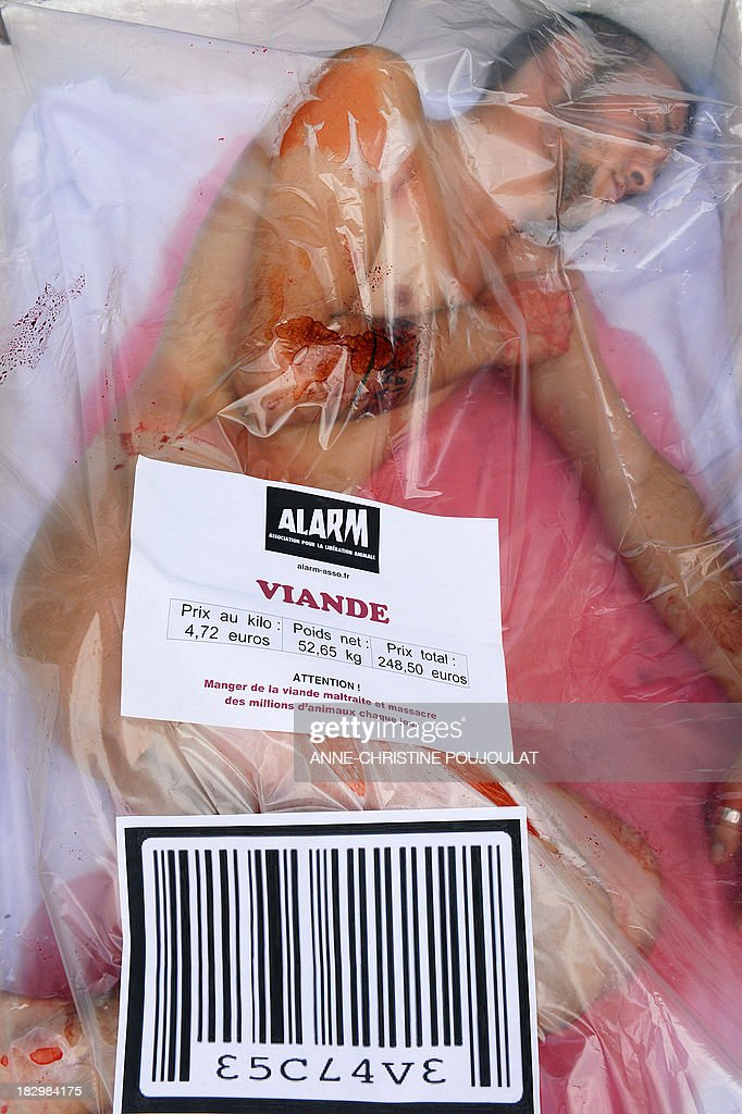 An animal rights activists from the association ALARM lays on punnet like a piece of meat to protest against animal exploitation as part of the International Vegetarian Week on October 3, 2013 in Marseille, southern France. AFP PHOTO / ANNE-CHRISTINE POUJOULAT