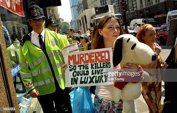An animal rights protester carries a banner during a protest against experimentation on animals at Huntingdon Life Sciences July 26 2001 at the...