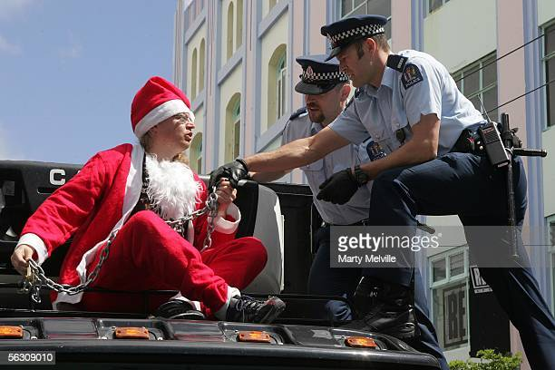 An animal rights protester dressed as Santa Claus and chained to the top of a truck carrying farm meat produce is arrested by police as he...