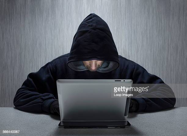 An anonymous hooded male using a tablet computer to represent a cyber criminal