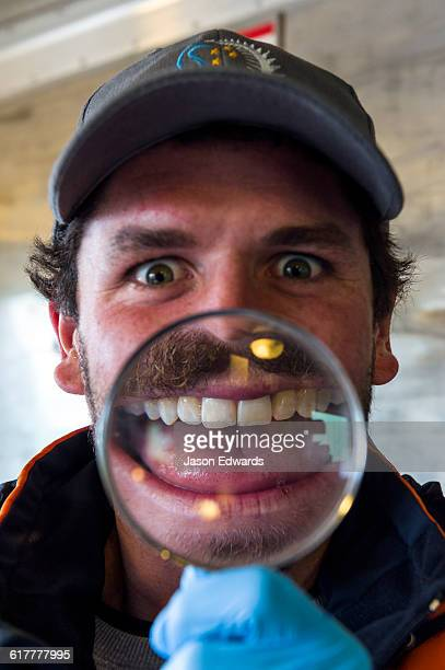 An Antarctic volunteer makes an enlarged distorted smiling face through a magnifying glass.