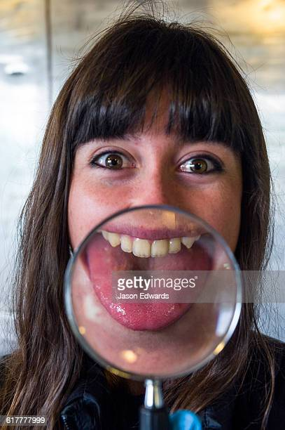 An Antarctic volunteer pokes her enlarged distorted tongue out through a magnifying glass.