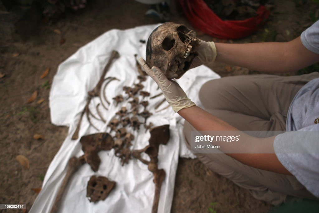 An anthropology student inspects the bones of a suspected undocumented immigrant after they were exhumed from a gravesite on May 22, 2013 in Falfurrias, Brooks County, Texas. In Brooks County alone, at least 129 immigrants perished in 2012, most of dehydration while making the long crossing from Mexico. Teams from Baylor University and the University of Indianapolis are exhuming the bodies of more than 50 immigrants who died, mostly from heat exhaustion, while crossing illegally from Mexico into the United States. The bodies will be examined and cross checked with DNA sent from Mexico and Central American countries, with the goal of reuniting the remains with families.