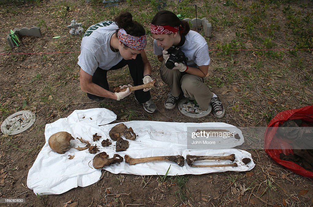 An anthropology team inspects the skeleton of a suspected undocumented immigrant after they exhumed the bones from a gravesite on May 22, 2013 in Falfurrias, Brooks County, Texas. In Brooks County alone, at least 129 immigrants perished in 2012, most of dehydration while making the long crossing from Mexico. Teams from Baylor University and the University of Indianapolis are exhuming the bodies of more than 50 immigrants who died during their journey. The bodies will be examined and cross checked with DNA sent from Mexico and Central American countries, with the goal of reuniting the remains with families.