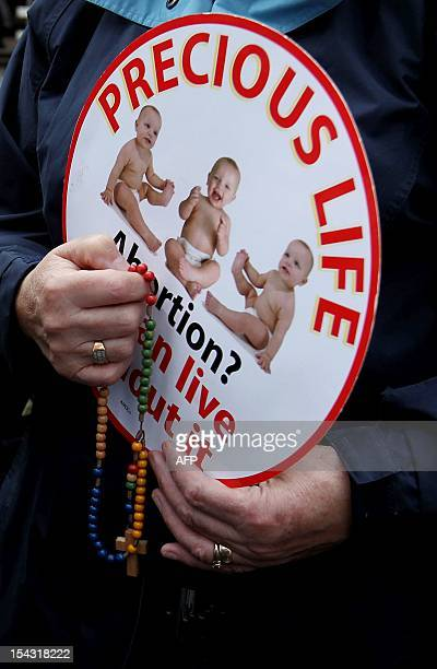 An anti abortion protestor holds a rosary while displaying a placard outside the Marie Stopes clinic the first private clinic to offer abortions to...