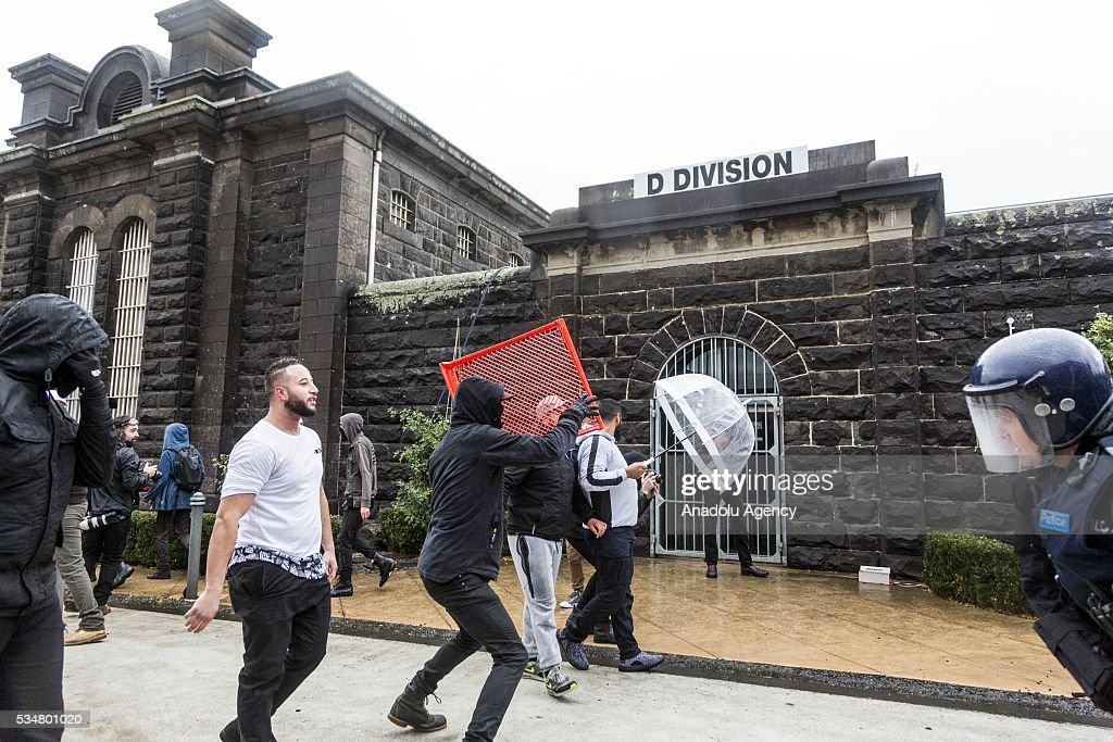 An Anti Fascists member in a mask throws a plastic crate over the police in front of Pentridge Prison D-Division block during a 'Say No To Racism' protest and a counter 'Stop the Far Left' rally in Coburg Melbourne, Australia on May 28, 2016. Seven men were arrested after a violent brawl erupted between rival protesters at an anti-racism rally in Melbourne's inner-north. Anti-Facists clashed with Anti-Islam nationalists who go by the name 'True Blue Crew'.