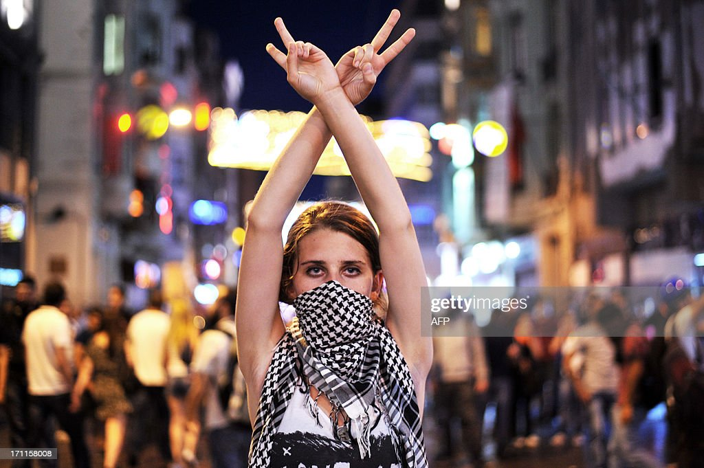 An anti goverment protester flashes a victory sign during the clashes between protestors and riot police on Taksim square in Istanbul on June 22, 2013. Turkish police used water cannon today to disperse thousands of demonstrators who had gathered anew in Istanbul's Taksim Square, calling for the resignation of Prime Minister Recep Tayyip Erdogan.