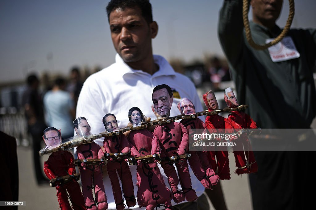 An anti Mubarak protester holds an effigy of Former Egyptian president Hosni Mubarak and his co accused outside the Egyptian police academy in Cairo, where Mubarak's trial is taking place on May 11, 2013. Former Egyptian president Hosni Mubarak appeared in court to face a new trial for complicity in the murder of hundreds protesters during the 2011 uprising. AFP PHOTO/GIANLUIGI GUERCIA