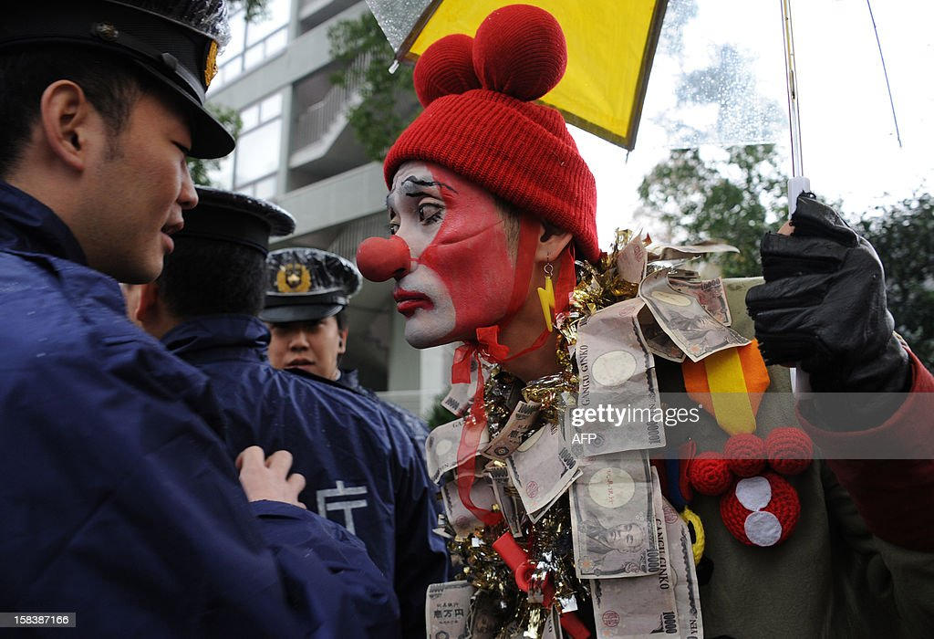 An anti nuclear activist (R) wearing a clown red nose and face paint designed to resemble the TEPCO logo stands next to police officers at an anti nuclear demonstration in Tokyo on December 15, 2012 as some 3,000 people hold a rally. High-level officials, including government ministers, from more than 50 countries and organisations gathered at Fukushima to hold a three-day international conference on nuclear safety. AFP PHOTO / Rie ISHII