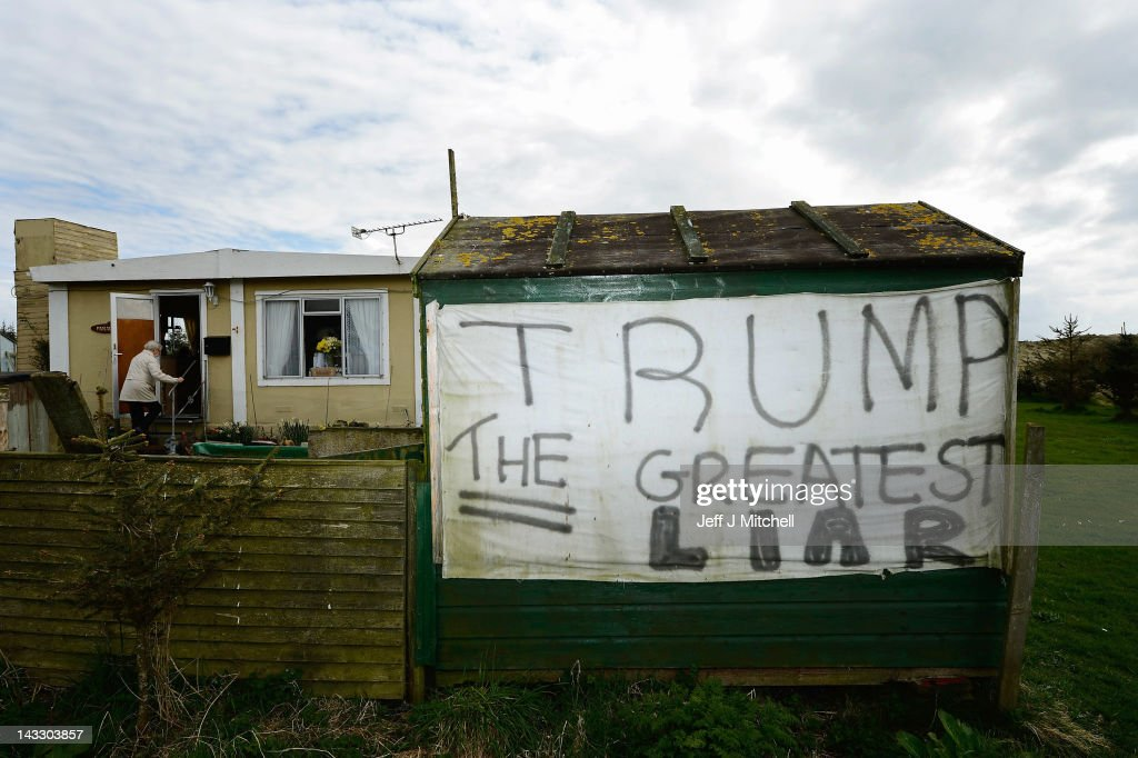 An anti Trump slogan is pinned to a shed at the home of Michael Forbes next to Donald Trump's golf course which is currently under construction on...