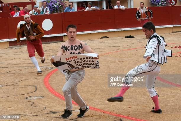 An antibullfighting protester with the words written on his chest in French 'Macron you can stop this' and holding a sign that reads 'No to the...