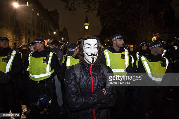 An anticapitalist protester wearing a Guy Fawkes mask stands in front of a line of British police officers during the 'Million Masks March' organised...