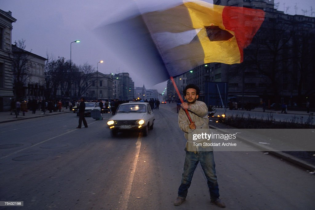 An anti-Ceausescu protestor waves a torn Romanian flag during the Romanian Revolution, December 1989. The Communist coat of arms has been removed from the centre of the flag.