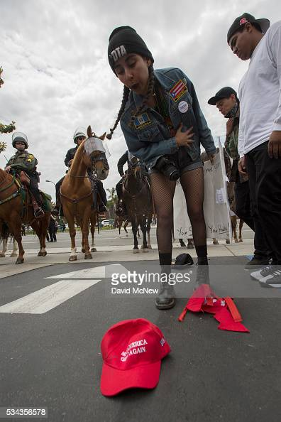 An antiDonal Trump protester spits on proTrump hat outside a campaign rally by presumptive GOP presidential candidate at the Anaheim Convention...