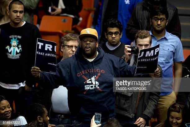 An antiDonald Trump protester tears a campaign sign during a Trump rally at the UIC Pavilion in Chicago on March 11 2016 Republican White House...