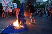 An antiEU protester burns an EU flag in front of the European Comission offices in Athens on July 2 during a demonstration supporting the no vote for...