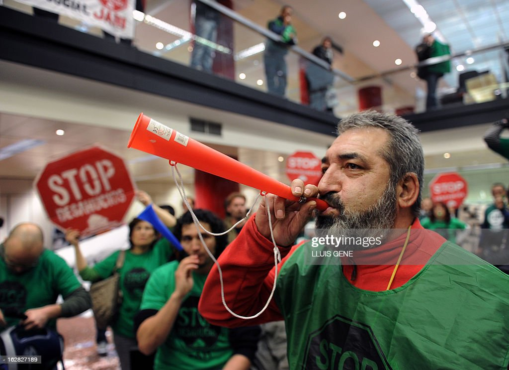 An anti-eviction activist blows a trumpet during a protest against evictions inside an office of Spanish bank Banco Popular in Barcelona on February 28, 2013.