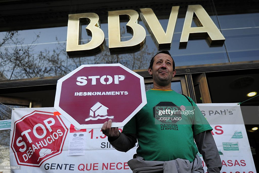An anti-eviction activist holds a banner reading 'Stop evictions' during a protest against mortgage debt organized by anti-eviction activists of the PAH (the Platform of People Affected by Mortgage) outside the BBVA Bank headquarters in Barcelona on February 7, 2013.