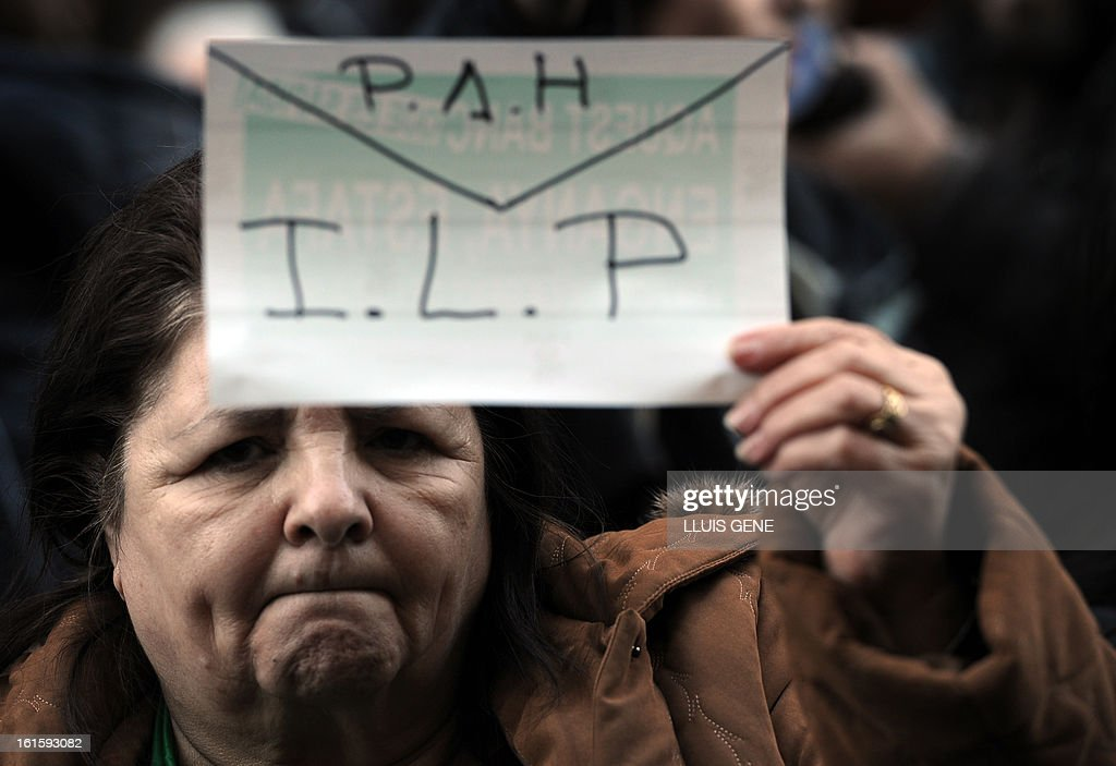 An anti-eviction activist holds a placard reading 'PAH' (the Platform of People Affected by Mortgage) and 'ILP' (Popular Legislative Initiative) as she takes part in a protest in front of the Popular Party's (PP) headquarters in Barcelona on February 12, 2013. AFP PHOTO/ LLUIS GENE