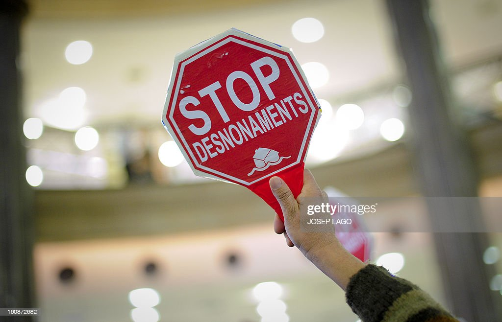 An anti-eviction activist holds a placard reading 'stop evictions' during a protest against mortgage debt organized by anti-eviction activists of the PAH (the Platform of People Affected by Mortgage) in the BBVA Bank headquarters in Barcelona on February 7, 2013.
