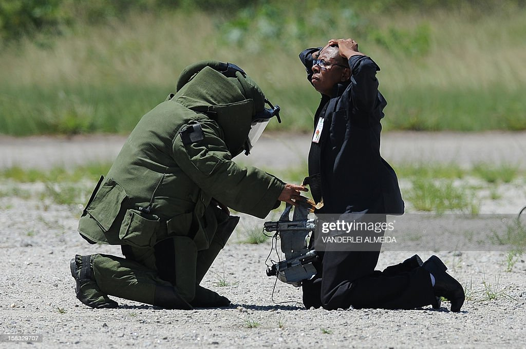 An anti-explosives expert from a police commandos from an anti-kidnapping unit, inspects a 'terrorist' loaded with explosives during a drill at the Tom Jobim International Airport in Rio de Janeiro, Brazil, on January 13, 2012, ahead of the FIFA World Cup Brazil 2014 and the 2016 Olympic Games.