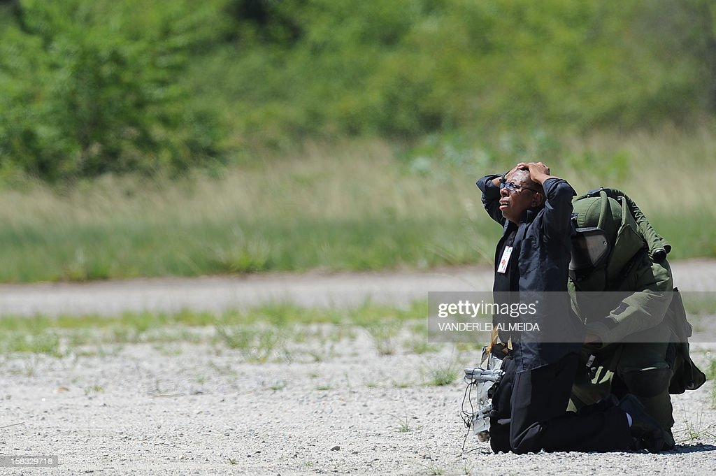 An anti-explosives expert from a police commandos from an anti-kidnapping unit, frisks a 'terrorist' loaded with explosives during a drill at the Tom Jobim International Airport in Rio de Janeiro, Brazil, on January 13, 2012, ahead of the FIFA World Cup Brazil 2014 and the 2016 Olympic Games.