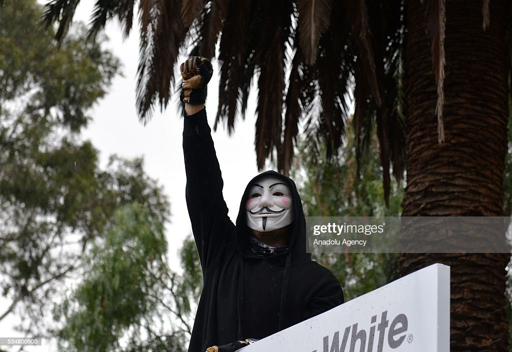 An antifascist protestor wearing a guy fawkes mask, clenches his fist in the air during a 'Say No To Racism' protest and a counter 'Stop the Far Left' rally in Coburg Melbourne, Australia on May 28, 2016. Seven men were arrested after a violent brawl erupted between rival protesters at an anti-racism rally in Melbourne's inner-north. Anti-Facists clashed with Anti-Islam nationalists who go by the name 'True Blue Crew'.