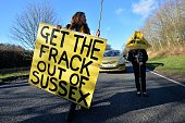 An antifracking and climate protesters hold placards during a rally at the former test drill site operated by British energy firm Cuadrilla Resources...