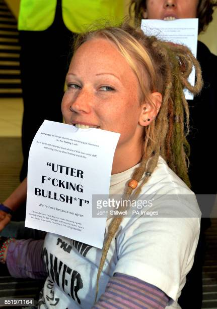 An antifracking demonstrator sits with a leaflet in her mouth and her hands superglued to other protesters at the offices of Bell Pottinger in High...
