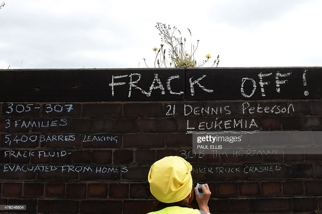 An antifracking demonstrator writes messages on a wall outside Lancashire County Hall in Preston northwest England on June 23 2015 during a...