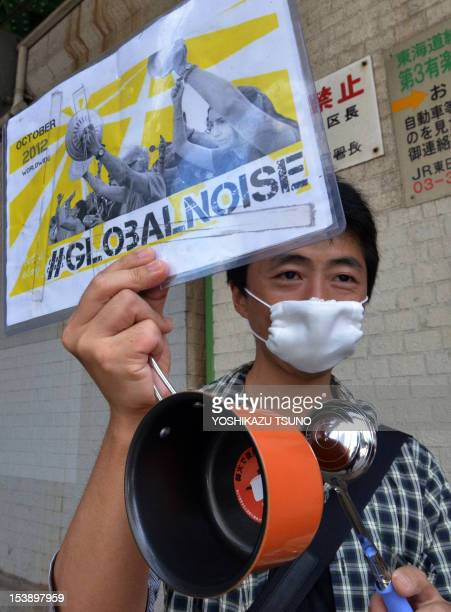 An antiglobalism activist holds up a placard as he joins others in protest outside of the annual meetings of the World Bank and International...