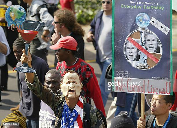 An antiglobalization activist wearing a George Bush mask and waving a glass filled with Earth's blood demonstrates with 10000 protesters out from...